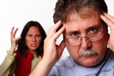 A man holding his head in the foreground while a woman gestures angrily behind him